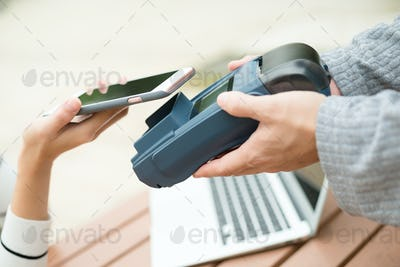 Woman pay the bill by mobile phone
