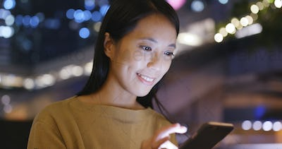 Young Woman use of mobile phone in Hong Kong at night