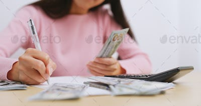 Woman counting the money at home