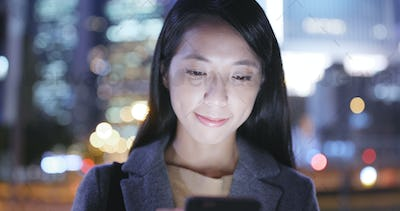 Asian Woman use of cellphone in city at night