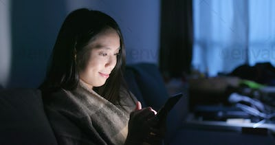 Woman use of mobile phone at home in the evening