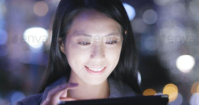 Woman uses a tablet computer at night