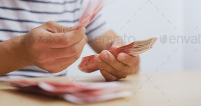 Man counting the number of RMB at home