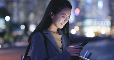 Asian Woman use of smart phone in city at night