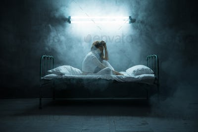 Depressed psycho woman sitting in bed, insomnia