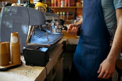 Male barista in apron prepares coffee on machine