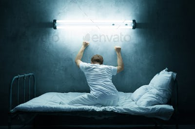 Psycho man alone in bed, dark room, hospital