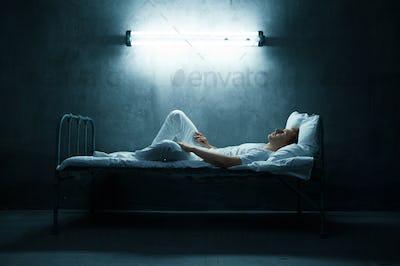 Psycho man lying in bed, dark room on background