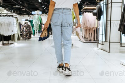 Young woman holds many shoes in clothing store