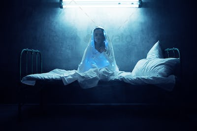 Mad woman in garlands sitting in bed, insomnia
