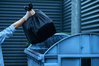 Volunteer puts plastic trash bag into the bin