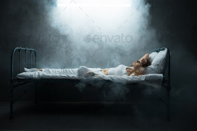 Psycho woman lying in bed, dark room on background