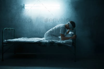Blindfolded psycho man sitting in bed, hospital