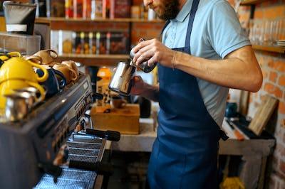 Male barista in apron prepares aroma coffee
