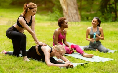 Young multinational ladies practicing yoga with trainer during outdoor class at park