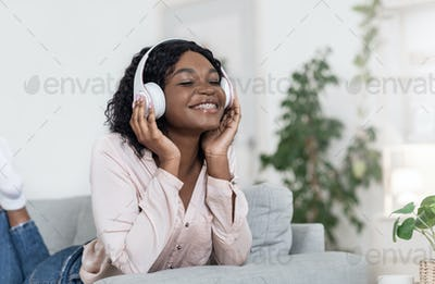Music Lover. Relaxed African Lady Enjoying Favorite Songs In Headphones At Home
