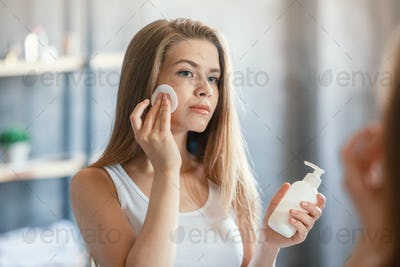 Pretty young female using facial tonic or makeup remover in front of mirror at bathroom