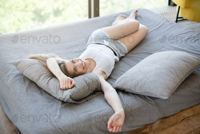 Smiling millennial woman lying on bed at home, enjoying her lazy weekend time