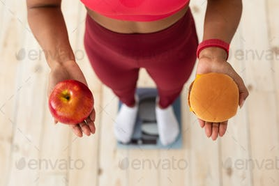Lady Choosing Between Burger And Apple Standing On Weight-Scales Indoor
