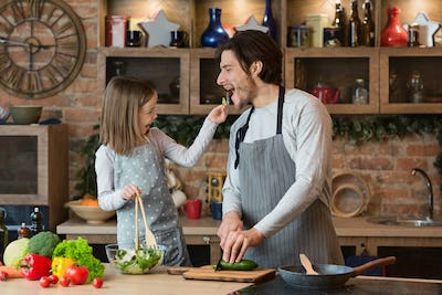 Happy Young Family Father And Daughter Having Fun While Cooking In Kitchen