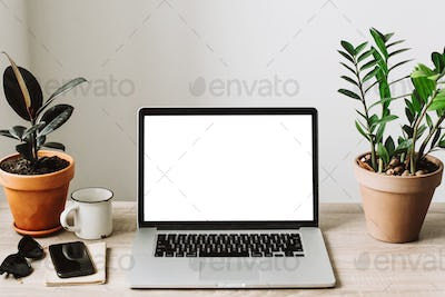 Laptop with empty screen on wooden desktop with phone, notebook, coffee and plant