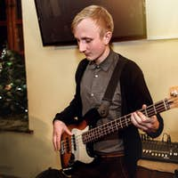 stylish bass guitarist playing on a concert on a background of his band