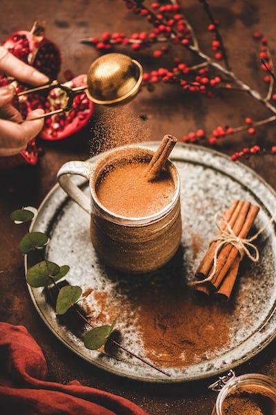 Human hand pouring cinnamon powder to turkish hot drink salep