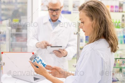 Young blond female pharmacist looking through information on big bottle of pills