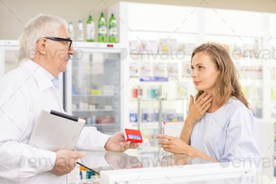 Young blond female client touching her sore throat while asking for medicaments