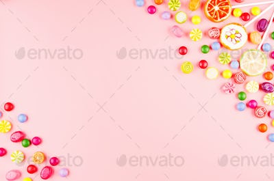 Flat lay view at sweet background of different type color and taste candies on pink. Space for text
