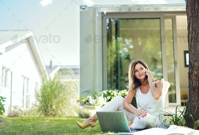 Mature woman working in home office outdoors in garden, using smartphone