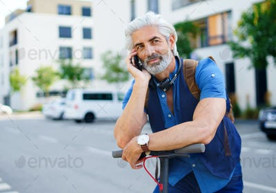 Mature man commuter with electric scooter outdoors in city, using smartphone