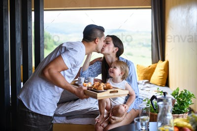 Young family with small daughter indoors, weekend away in container house in countryside