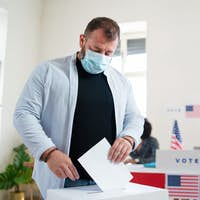 Mature man putting his vote in the ballot box, usa elections and coronavirus