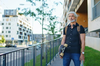 Portrait of mature man with skateboard outdoors in city, going back to work