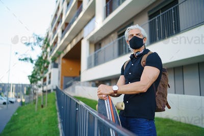 Mature man commuter with face mask and skateboard outdoors in city, coronavirus concept