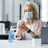 New normal and hygiene in office during coronavirus epidemic. Girl worker in protective mask with