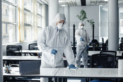 People in hazmat, protective mask and glasses making disinfection of furniture in office with