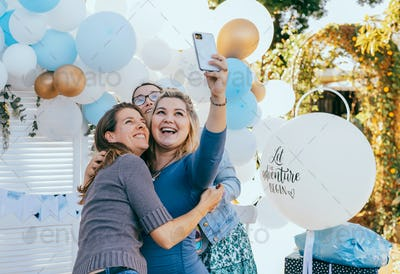 Female friends taking selfie with pregnant woman at a baby shower
