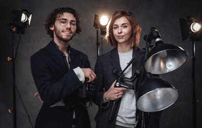 The team of two photographers holds a digital camera and lighting equipment posing in studio