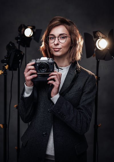 Beautiful redhead female photographer holds a digital camera and looking on the camera
