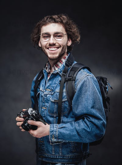 Portrait of a handsome young photographer with curly hair wearing denim jacket holds a camera