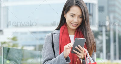 Shopping woman holding paper bag and use of mobile phone