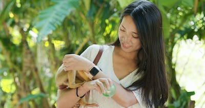 Woman feed Squirrel Monkeys in the park
