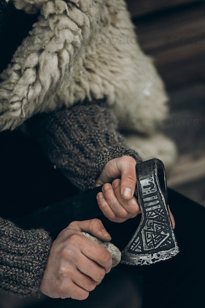 Brave viking warrior sharpening axe before battle in the north