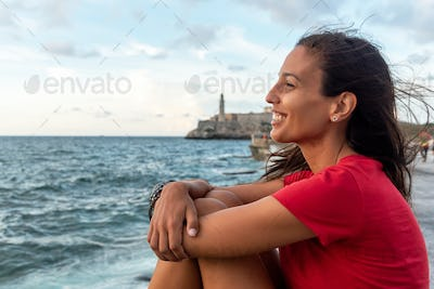 Portrait of tourist woman relaxing on The Malecon, Havana