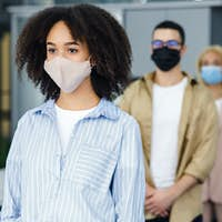New normal and temperature check before work. Millennial multiracial employees in protective masks