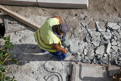 Construction worker with jackhammer drilling concrete on sidewalk