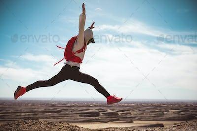 Woman trail runner cross country running  on sand desert dunes