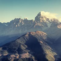 Autumn landscape and snow-capped mountain peaks. View of the mou